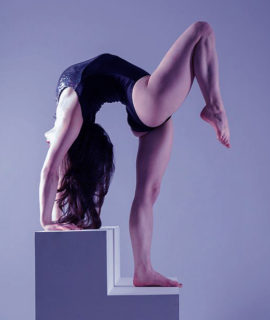 Acrobatics image. LDA teacher Pixie LeKnot in back bend on stairs for lingerie shoot with purple tinge background